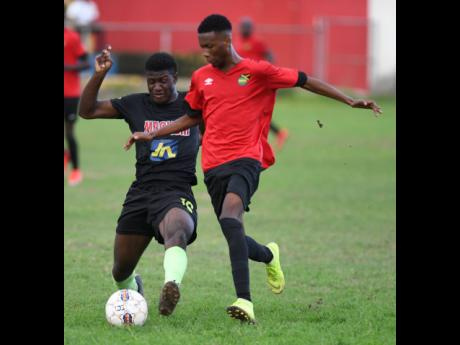 Jermaine Reid (left) of Molynes United goes into a challenge with Lime Hall FC player Shaquill Wallace in the JFF All-Island Confederations Play-Offs at the Constant Spring Field yesterday.Ricardo Makyn/Chief Photo Editor