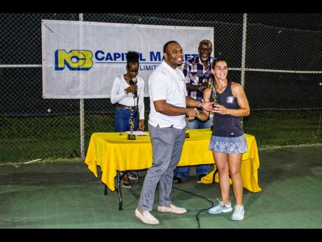 Sarah Lizariturry receives her Liguanea Club Tennis Classic trophy from Roland Henry, senior marketing officer at NCB Capital Markets, the major sponsor of the competition. At the table are Llockett McGregor, the tournament organiser, and Kimberley McGregor.