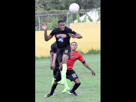 Molynes United's Akeem Stewart (left) gets aerial to clear a ball from Downs United's Ajay Chin (right) during their JFF All-Island Confederation Play-Offs match at the Constant Spring Field yesterday.