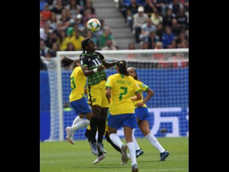 Jamaica's Khadija Shaw (left) beats Brazil's Andressa to a header during their Group C clash in the FIFA Women's World Cup at the Stade des Alpes in Grenoble, France, on Sunday. The Reggae Girlz lost 3-0.