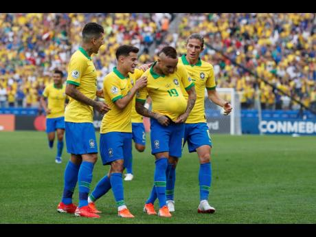 Teammates congratulate Brazil's Everton (second right) after he scored his side's third goal against Peru during a Copa América Group A soccer match at the Arena Corinthians in Sao Paulo, Brazil, yesterday. Brazil won 5-0.