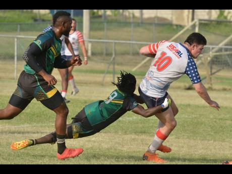 Jamaica Reggae Warriors player Steve Miller (centre) tackles USA Hawks' Kyle Denham (right) during their rugby league test match at the UWI Mona Bowl on Saturday.