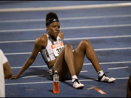 Danielle Williams sits on the track moments after officials decide to move on to the men's 110m hurdles, as a result of two false starts in the women's 100m hurdles final, at the JAAA/Supreme Ventures National Senior Athletics Championships at the National Stadium last night.