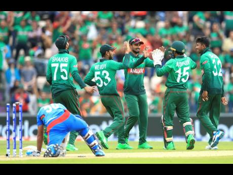 Bangladesh celebrate taking the wicket of Afghanistan's Hashmatullah (left) during their ICC World Cup group stage match at the Hampshire Bowl, Southampton, England, yesterday.
