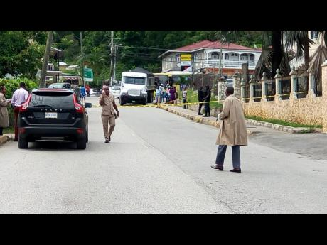 Police officers processing the murder scene where two men were hit, one fatally, in Anchovy, St James, yesterday.