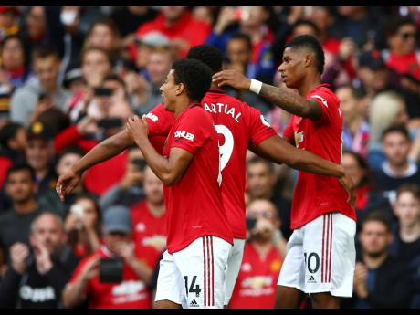 Manchester United's Marcus Rashford (right) celebrates with teammates after scoring his side's first goal during the English Premier League match against Chelsea at Old Trafford in Manchester, England, on Sunday. Manchester United won 4-0.