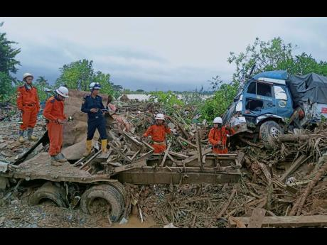 Members of a Myanmar rescue team work at a landslide-hit area in Paung township, Mon State, Myanmar, on Monday.