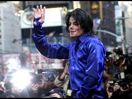 In this 2001 file photo, Michael Jackson waves to crowds gathered to see him at his first-ever in-store appearance to celebrate his new album, 'Invincible' in New York.