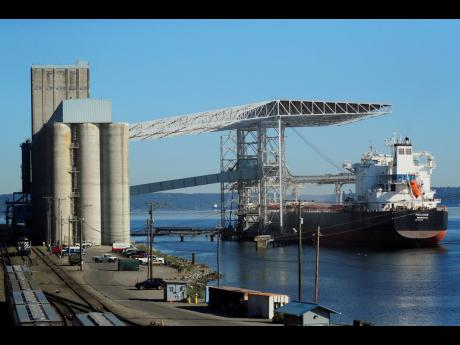 In this May 10, 2019, file photo a bulk carrier ship is loaded at the Temco grain terminal at the Port of Tacoma in Washington. US-China trade tensions are driving fears of recession.