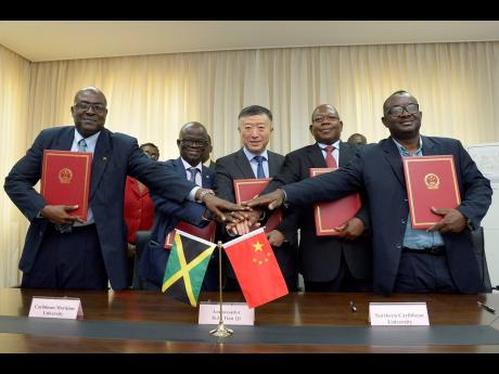 Chinese Ambassador Tian Qi (centre) shares an iconic moment with (from left) ACP Ronald Anderson, director of the National Police College of Jamaica; Professor Ibrahim Ajagunna, acting president of the Caribbean Maritime University; Dr Lincoln Edwards, president of Northern Caribbean University; and Michael Ellis, principal of Cornwall College, following a signing ceremony of an agreement for the provision of Chinese language teachers to the institutions at the Chinese Embassy in Kingston on Thursday.