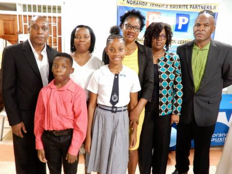 Top-performing Primary Exit Profile examinations boy and girl in Noranda's operating area in St Ann, Jamari Green and Abrianna Greaves (front), are joined by (from left) Delroy Dell, vice-president and general manager, Noranda Bauxite; Jamari's mother Christine Green, Abrianna's mother Normalyn Smith-Greaves,  Nordia Tracey, human resource manager, Noranda; and Kent Skyers, community relations superintendent, Noranda.