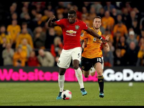 Manchester United's Paul Pogba (left) comes under pressure from Wolverhampton Wanderers' Diogo Jota during the teams' English Premier League match at the Molineux Stadium in Wolverhampton, England, yesterday. The match ended 1-1.