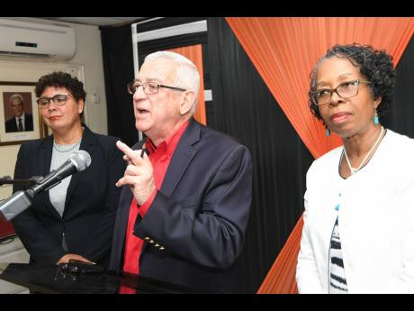 Opposition Spokesperson on Education Ronald Thwaites addresses journalists at the People's National Party (PNP) headquarters in  St Andrew yesterday. Chairman of the PNP Commission on Education, Elaine Foster Allen (right), and Patricia Sutherland look on.