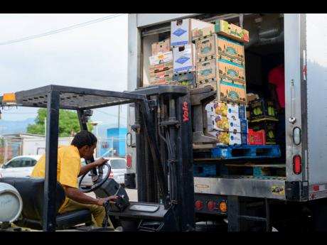 A forklift operator loads goods on to a truck at Everything Fresh Limited in Kingston. FILE