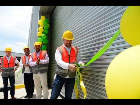 Operations Director Fenton Wheelock cuts the ribbon to Celebration Brands' new warehouse facility, Logic One, located at the Pepsi-Cola Jamaica complex in Kingston, on Tuesday, August 20, 2019. The others (from left) are outgoing Managing Director of Red Stripe Ricardo Nuncio; Anthony Hylton, member of parliament for Western St Andrew; and Managing Director of Celebration Brands Edwin Vaquerano.