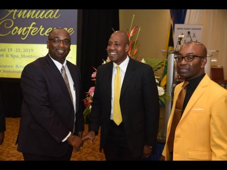 Ryan Parkes (centre), chief of business banking and public sector engagement at JN Bank, in conversation with Dr Garth Anderson (left), outgoing president of the Jamaica Teachers' Association (JTA), and Owen Speid, new president of the JTA.