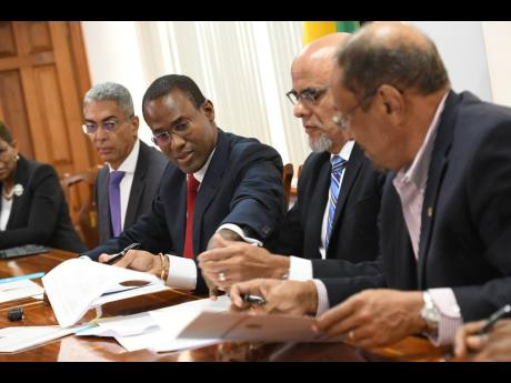 From left: Richard Byles, governor of the Bank of Jamaica, looks on as Finance Minister Nigel Clarke points something out to Keith Duncan, chairman of the Economic Programme Oversight Committee, and Howard Mitchell, president of the Private Sector Organisation of Jamaica, at yesterday's signing ceremony bto extend domestic monitoring of the country's economic reform programme.
