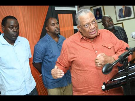 People's National Party President Dr Peter Phillips speaking to members of the media yesterday as PNP Deputy General Secretary Basil Waite (left), General Secretary Julian Robinson (second left) and Chairman Fitz Jackson look on.