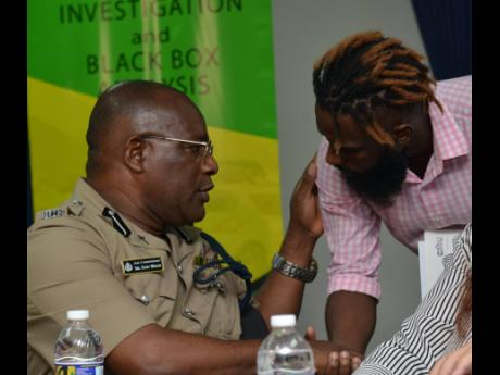 Head of the Public Safety and Traffic Enforcement Branch, Assistant Commissioner of Police Bishop Dr Gary Welsh, speaks with Maleek Powell, who lost his sister in a fatal motor vehicle accident, during yesterday's International Symposium on Traffic Crash Investigation and Black Box Analysis at Caribbean Maritime University.