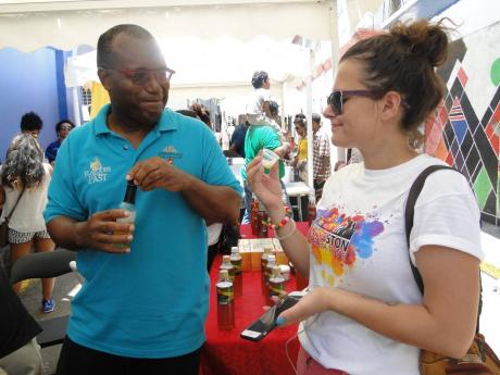 Stredie Thompson (left), managing director at Journeys End Wine Company Limited, makers of Flavours of the Past, looks on as a patron is about to sample a 'flavour of the past' at a recent event in downtown Kingston.