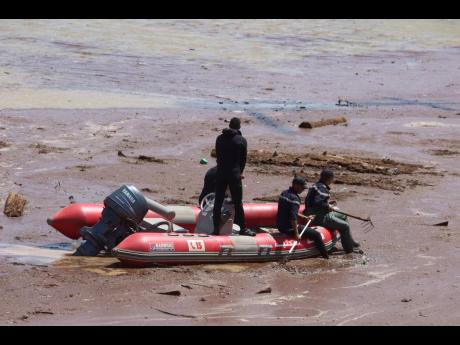 A rescue boat navigates the muddy waters in the ongoing search. Below: Security forces gather to begin the search for victims of the bus crash.