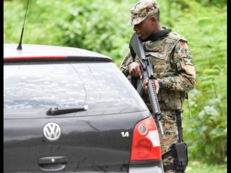 A Jamaica Defence Force soldier speaks with a motorist at a state of emergency checkpoint in Sevens Heights, Clarendon, last Thursday.