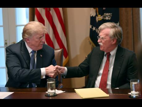 In this April 9, 2018 photo, President Donald Trump, left, shakes hands with national security adviser John Bolton in the Cabinet Room of the White House in Washington at the start of a meeting with military leaders.  Trump has fired national security adviser John Bolton. Trump tweeted Tuesday that he told Bolton Monday night that his services were no longer needed at the White House.