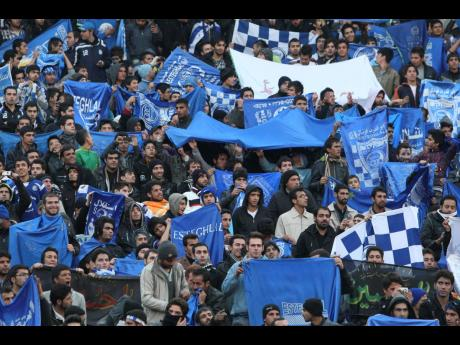In this December 9, 2011 file photo, supporters of Iranian soccer team Esteghlal, hold flags of their favourite team, at the Azadi (Freedom) stadium, in Tehran, Iran.