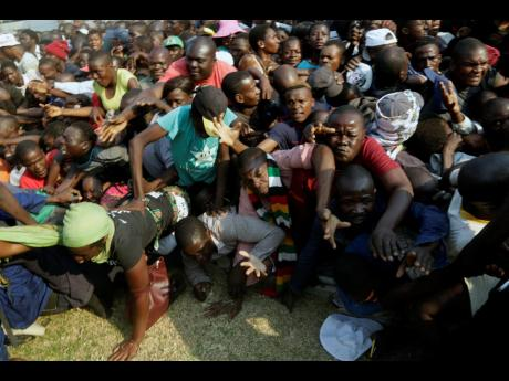 Mourners stampede after the arrival of the coffin carrying former President Robert Mugabe at the Rufaro Stadium in Harare on Thursday, September 12, where Mugabe will lie in state for a public viewing.