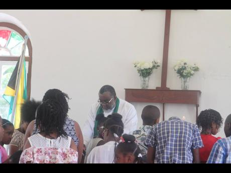 Reverend Shaun Nisbeth praying for the children recently at the St Stephen's Anglican Church in Chantilly.