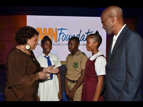 Dr Joy Spence (left), master bender, J. Wray and Nephew, and Clement 'Jimmy' Lawrence (right), chairman JWN Foundation, chat with Mickayla Downer (second left), student from Immaculate Conception High School; Dontae Downer (centre) from Calabar High and Abbigaye Cole (second right) from Glenmuir High School. The students received scholarship awards from the JWN Foundation at a ceremony which was held at the Courtleigh Auditorium, last week.
