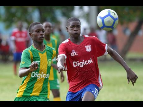 Shorn Hector/Photographer  Jevaughn Rose (left) of Edith Dalton James High challenges Camperdown High's Rasheed Grant for a loose ball during  their ISSA/Digicel Manning Cup encounter at the Alpha Boys' Home football field yesterday. Camperdown won 2-0.