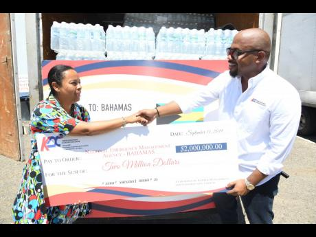 Karl Tulloch, director of Kemtek Development and Construction Limited, presents a cheque for $2 million to The Bahamas Consulate's honorary consul, Alveta Knight, last Friday.