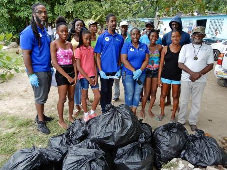 A pleased Kelvin Archer (right), president of the Rio Nuevo and Stewart Town Fishing Association in St Mary, members of the Kiwanis Club of Charlton-Alexandria; members of the St Hilda's Diocesan High School Key Club; and fishermen from the association stand alongside some of the garbage collected on Saturday.