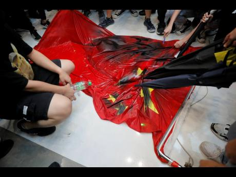 Protesters vandalize a Chinese national flag during a protest at a mall on Sunday in Hong Kong. Hong Kong's pro-democracy protests, now in their fourth month, have often descended into violence in the evenings.  (AP)