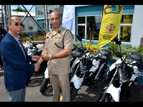 National Security Minister Dr Horace Chang (left) hands over the keys for a batch of 80 new motorcycles  acquired for the Jamaica Constabulary Force's Public Safety and Traffic Enforcement Branch to Police Commissioner Major General Antony Anderson. The presentation was made during a ceremony at the Office of the Commissioner of Police in Kingston, on September 20.
