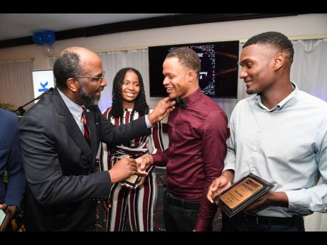 Earl Jarrett (left), chief executive officer, the Jamaica National Group, adjusts the bow tie of Kemar Titus (second right), JN WAY Scholarship recipient, as Shonnoya Houston, Most Improved Ambassador, and Clive Lindo, Team Leader of the Year, look on. The occasion was JN Bank's Wise Aspiring Youth (JN WAY) awards ceremony, held at The Jamaica Pegasus hotel in New Kingston on September 14.