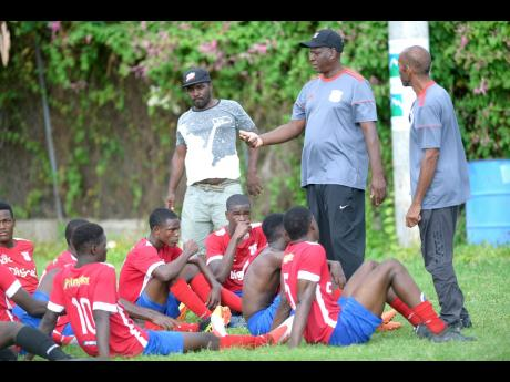 Camperdown High's coach Christopher Bender (second right) speaks with his players during the half-time break in their ISSA/Digicel Manning Cup encounter  against Edith Dalton James High at the Alpha Boys' Home football field last Saturday. Camperdown won 2-0.