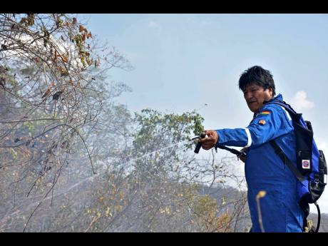 Bolivian President Evo Morales sprays water on a fire burning on the outskirts of Robore, Bolivia. Memes have gone viral in Bolivia showing Morales combating forest fires with a toy water gun or a flame-thrower, while others superimpose his image on the original cast of the 'Ghostbusters' film, as a way to poke fun at South America's longest-serving leader and his delayed response to forest fires.