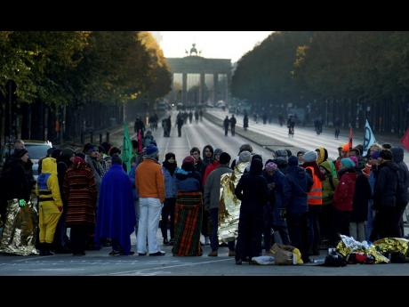Supporters of the 'Extinction Rebellion' movement block a road between the Brandenburg Gate, background, and the Victory Column in Berlin, Germany, Monday, October 7. The activists want to draw attention on the climate protest by blocking roads and with other acts of civil disobedience in Berlin and other cities around the world.