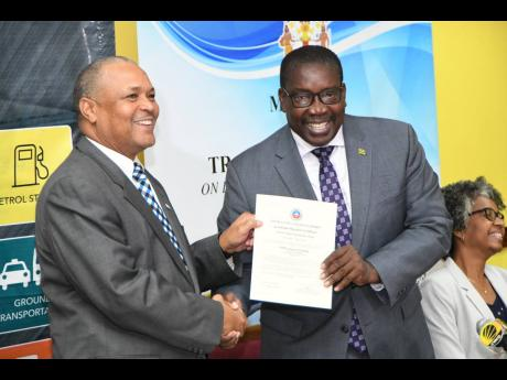 Transport Minister Robert Montague (right) hands over the airport operators certification to Audley Deidrick, president of the Airports Authority of Jamaica and CEO of Norman Manley International Airport Limited. The Jamaica Civil Aviation Authority, as regulators of Jamaica's aviation industry, officially handed over the certificate at the offices of the Ministry of Transport and Miningin St Andrew yesterday.