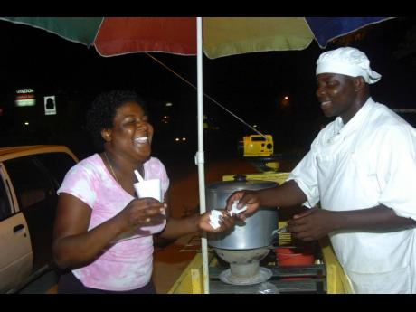 Owen Buddle cracks a joke with Stacy Bremmer while serving her a cup of vegetable soup along the Negril main road in Westmoreland in this 2006 Gleaner file photo.