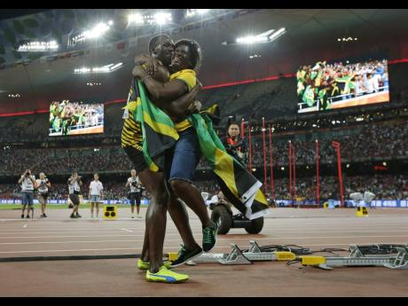 In this 2015 photo 2015, Usain Bolt hugs his mother, Jennifer Bolt, after victory in the men's 100m final at the IAAF World Championships at the Bird's Nest Stadium in Beijing, China.