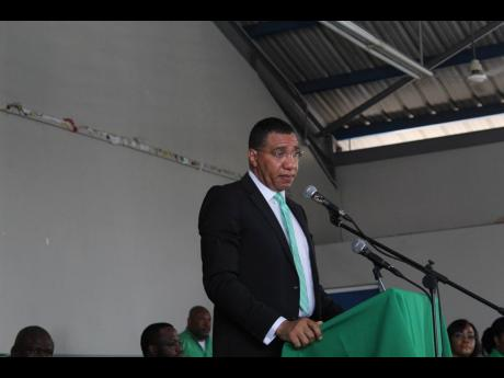 Prime Minister Andrew Holness, leader of the Jamaica Labour Party, addresses an Area Council One meeting at the Girl Guides Association of Jamaica headquarters in St Andrew yesterday.