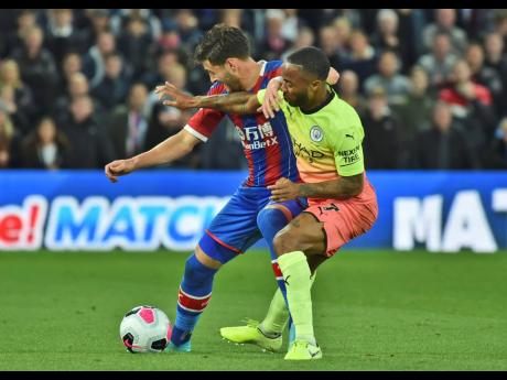 Manchester City's Raheem Sterling (right) fights for the ball with Crystal Palace's Joel Ward during the English Premier League match between Crystal Palace and Manchester City at Selhurst Park in London, England, yesterday. City won 2-0.