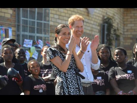 In this Monday, September 23 photo, Britain's Prince Harry and Meghan, Duchess of Sussex, greet youths on a visit to the Nyanga Methodist Church in Cape Town, South Africa, which houses a project where children are taught about their rights, self-awareness and safety. Self-defence classes and female empowerment training to young girls in the community are provided