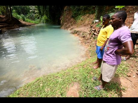 Residents of Zephyrton, just outside of Linstead in St Catherine, look at the discoloured Rio Cobre in July last year as it is contaminated by waste from the Windalco bauxite plant.