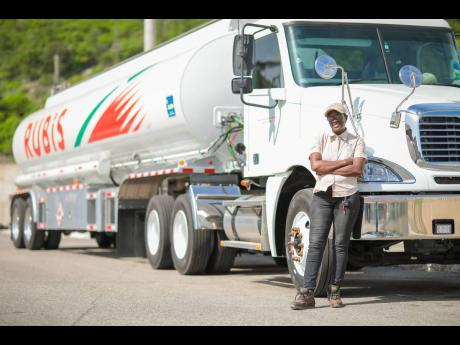Carol Clarke poses alongside a RUBiS trailer truck.