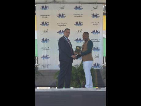 Former police Corporal Clive 'Karate Georgie' Lawrence (right) receives the 2019 Mayor's Special Award from Montego Bay Homer Davis during the 2019 National Heroes Day Civic Awards Ceremony on Monday.