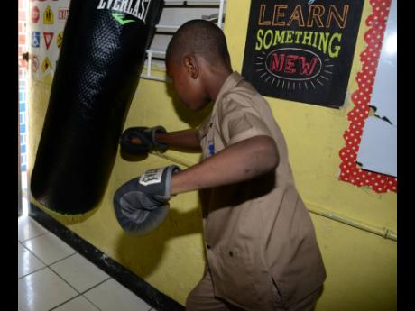 A student at St Aloysius Primary School in Kingston demonstrates how the punching bag is used as part of a therapy for pupils at the insitution.